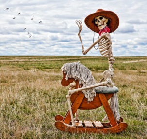 Skeleton cowboy riding a rocking horse in a field.